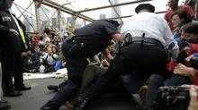 Police officers reach into a crowd of protesters to make an arrest on the Brooklyn Bridge during an Occupy Wall Street march in New York October 1, 2011. (JESSICA RINALDI/Reuters)