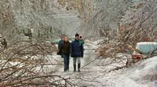Pedestrians make their way past downed trees as an ice storm ripped through Montreal in this Jan. 6, 1998 photo. The ice storm left parts of Quebec and Ontario without electricity for days as ice-covered trees crashed down on power lines. (RYAN REMIORZ/Canadian Press/RYAN REMIORZ/Canadian Press)