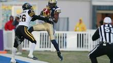 Winnipeg Blue Bombers' Cory Watson, right, catches a pass in the end zone in front of Hamilton Tiger-Cats' Matt Bucknor, buts steps out of bounds, during the first half of their CFL game in Winnipeg on September 21, 2012. (John Woods/THE CANADIAN PRESS)
