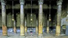 A girl runs between the poles of the Church of the Nativity, traditionally believed by many to be the birthplace of Jesus Christ, in the West Bank town of Bethlehem, Tuesday, May 5, 2009. (MUHAMMED MUHEISEN/Muhammed Muheisen / AP)