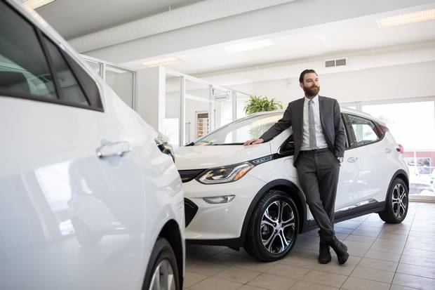 Hugo Jeanson, co-owner of Bourgeois Chevrolet, poses for a photograph with a Chevrolet Bolt electric car at the car dealership in Rawdon, Quebec, 70 kilometres north of Montreal, on Thursday, February 8, 2018. This dealership in a small town in Quebec sells the most electric and hybrid vehicles in Canada.