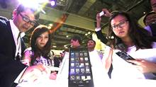 Visitors try out the Huawei Ascend P6 Android-based smartphones during their launch at the CommunicAsia communication and information technology exhibition in Singapore. (EDGAR SU/REUTERS)