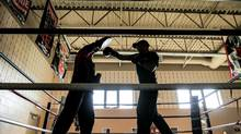 Physical activities such as boxing and rock climbing are part of the military themed education at Robert Land Academy in Wellandport, Ont. Sergeant Major Paul Zahra, right, puts one his charges through a boxing drill. (Glenn Lowson for The Globe and Mail)