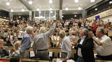 Former CERN director general Christopher Llewelyn-Smith, standing left, Lyn Evans, scientific director, standing second left, Herwig Schopper, standing center, Luciano Maiani, standing second right, and Robert Aymard, standing right, wave after the presentation of results during a scientific seminar to deliver the latest update in the search for the Higgs boson at the European Organization for Nuclear Research (CERN) in Meyrin near Geneva, Switzerland. (Denis Balibouse/AP)