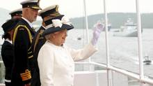 The Queen waves from the deck of the frigate HMCS St. John's as she sails past one of the 28 warships in Halifax Harbour on Tuesday. (Paul Darrow/Reuters/Paul Darrow/Reuters)