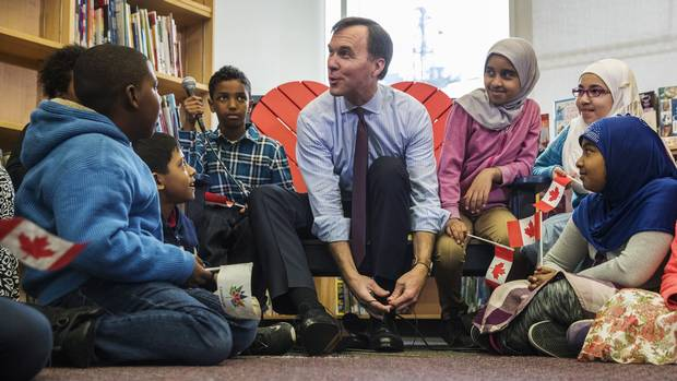 Canada's federal Finance Minister Bill Morneau takes part in the pre-budget ceremony of putting on new shoes, at the Nelson Mandela Park Public School in Toronto on March 20, 2017.