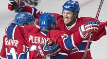 Montreal Canadiens' Tomas Plekanec, centre, celebrates with teammates Brandon Prust, right, and Brendan Gallagher after scoring against the Tampa Bay Lightning during third period NHL Stanley Cup playoff action in Montreal, Sunday, April 20, 2014. (The Canadian Press)