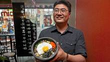 Sam Lee, owner of restaurant Bi Bim Bap holds up the traditional bibimbap dish (Jennifer Roberts for the Globe and Mail/Jennifer Roberts for the Globe and Mail)