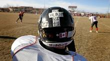 Warriors running back Marcus Cooper wears the initials of his teammates Vincent Stover 16, Matt Deller, 16, Walter Borden - Wilkins 15, and Tanner Hildebrand, 15, who were killed and Zach Judd who was injured in a car accident in Grande Prairie on Saturday, October 22, 2011. (Jason Franson/The Globe and Mail/Jason Franson/The Globe and Mail)