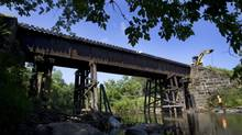 A work crew removes encroaching trees and deadfall around a Cowansville, Que., bridge that has become a symbol of safety concerns. (Peter Power/The Globe and Mail)