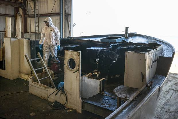 An employee at the A.F. Theriault & Son Ltd. boatyard begins stripping the fire-damaged sections of the lobster boat