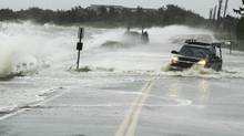 A truck drives through water pushed over a road by Hurricane Sandy in Southampton (Lucas Jackson/Reuters)