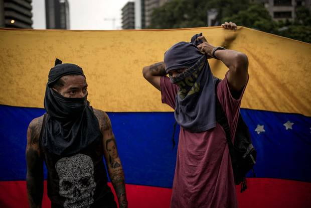 Two protesters get ready moments before clashing with Venezuelan security forces in Caracas.