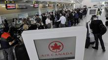 Passengers wait in line for an Air Canada flight at Toronto's Pearson airport, March 18, 2012. (J.P. Moczulski/The Globe and Mail)