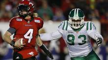 Calgary Stampeders' quarterback Drew Tate (L) rolls away from Saskatchewan Roughriders' Tearrius George during the second half of their West Division semi-final CFL football game in Calgary, Alberta, November 11, 2012. (Reuters)
