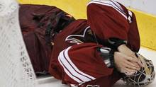 Phoenix Coyotes' Mike Smith falls to the ice after being hit during action against the Chicago Bla