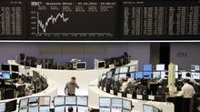 Traders are pictured at their desks in front of the DAX board at the Frankfurt stock exchange March 7, 2012. (KIRILL IORDANSKY/KIRILL IORDANSKY/REUTERS)