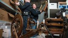 Constable Darryl Morgan, right, and Sgt. Colin Maclean of the RCMP examine a storage unit full of items stolen by John Mark Tillmann. Constable Morgan says he found Mr. Tillmann's marked-up guide of antique shops across Atlantic Canada and called the stores to see if anything was missing. 'Each and every one of them had something [missing].' (SCOTT MUNN For The Globe and Mail)