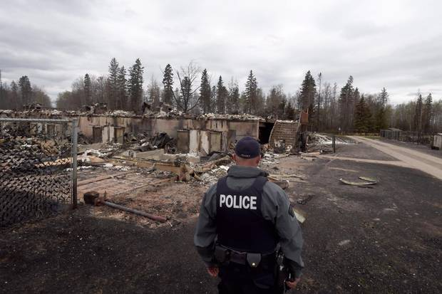A police officer looks over a fire-damaged building in the Abasand neighbourhood in Fort McMurray, Alta., on May 9, 2016.