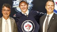 Jacob Trouba, center, a defenseman, stands with officials from the Winnipeg Jets after being chosen ninth overall in the first round of the NHL draft on Friday, June 22, 2012, in Pittsburgh. (Keith Srakocic/AP)