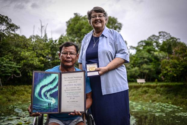 Tun Channareth, left, and Sister Denise Coghlan, from the International Campaign to Ban Landmines, stand in front of a crater made by a bomb dropped over Cambodia during its wartime years. Mr. Channareth, whose legs were severed by a landmine in 1982, travelled to Oslo in 1997 to receive the Nobel Peace Prize on behalf of the ICBL for its advocacy against landmines.