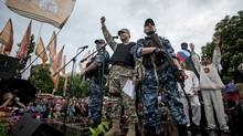 Pro-Russian gunmen and activists react while listening to a speaker as they declare independence for the Luhansk region in eastern Ukraine on Monday, May 12, 2014. Pro-Russia separatists in eastern Ukraine declared independence Monday for the Donetsk and Luhansk regions following their contentious referendum ballot. (Evgeniy Maloletka/AP)
