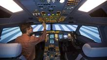A technician operates a CAE A330-200 passenger plane flight simulator at the Lufthansa Flight Training centre in Berlin. (THOMAS PETER/REUTERS)