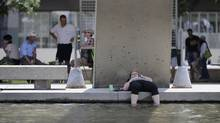 The waters of the reflecting pool at Nathan Phillip Square offers a cooling break for this woman as she soaks her feet in the water during a lunch break on June 20 2012. Hot, humid weather smothered Toronto and southern Ontario for another day with humidex readings into the 40's. (Fred Lum/The Globe and Mail)