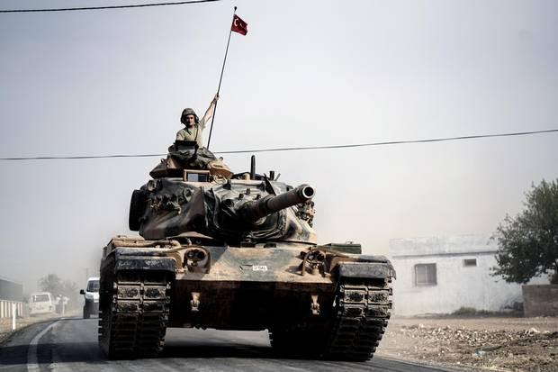 Turkish army tanks and armored personnel carriers move toward the Syrian border, in Karkamis, Turkey, on Aug. 25, 2016.