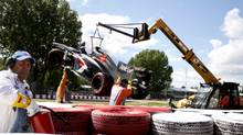 A crane carries the Sauber Formula One car of Esteban Gutierrez off the track following the Canadian F1 Grand Prix at the Circuit Gilles Villeneuve in Montreal June 9, 2013. A race-track worker was killed after he slipped under the wheel of the crane at the end of the event. (CHRISTINNE MUSCHI/REUTERS)