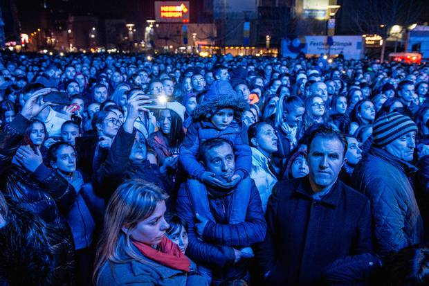 Kosovars watch Pristina-born British singer Rita Ora perform on one of dozens of big screens that was set up to watch a free concert celebration of the Kosovo's 10th anniversary in the capital on Feb. 17, 2018. The show, which ended with a massive fireworks display, was headlined by Ora who is considered an icon in Kosovo.