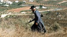 An armed ultra-orthodox Jewish settler walks in the mountains overlooking the Palestinian village of Burin in the West Bank. (MENAHEM KAHANA)