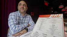 Massimo Lecas, co-owner of buonanotte restaurant, poses for a photograph with a menu at the restaurant in Montreal, Wednesday, February 20, 2013. The Office quebecois de la langue francais has warned a Montreal restaurant owner there's too much Italian on the menu of his Italian restaurant. (GRAHAM HUGHES/THE CANADIAN PRESS)