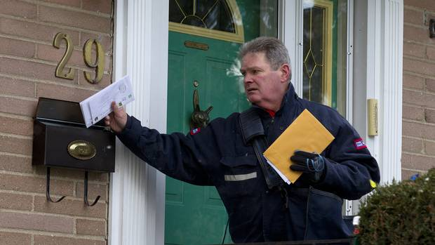 Mail carrier Leo Gaspari delivers mail on his route in the Don Mills and Lawrence area in Toronto on Dec. 11, 2013.