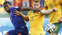 Georginio Wijnaldum of the Netherlands fights for the ball with Australia's Oliver Bozanic during their 2014 World Cup Group B soccer match at the Beira Rio stadium in Porto Alegre June 18, 2014. (STEFANO RELLANDINI/REUTERS)