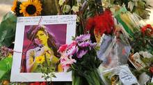 Flowers, pictures and messages are left in tribute to late soul music and British pop star Amy Winehouse, near her home in London, on July 25, 2011. (BEN STANSALL/AFP/Getty Images)