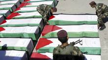 Members of the Palestinian security forces place a coffin on the ground containing the remains of one of 91 Palestinian militants transferred from Israel to the Palestinian Authority, in the West Bank city of Ramallah, Thursday, May 31, 2012. (Mohammed Ballas/Associated Press)