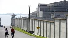 Pedestrians walk past the outer walls of the recently closed Kingston Penitentiary on Oct. 2. About two dozen people entered its imposing limestone confines – the first in a series of tour groups allowed inside since the last prisoners were moved out. (Frank Gunn/The Canadian Press)