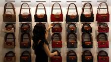 A worker at a store for French luxury leather goods maker Longchamp adjusts a display in Beijing in a file photo. China was once a gold mine for watch, car and jewellery companies, but a recent government campaign has hit sales of all three. (© David Gray/REUTERS)