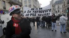 Striking workers of the French car manufacturer PSA Peugeot Citroen hold a banner that reads: 'No to the Closure of PSA Aulnay' in Paris Feb. 14, 2013. (Christophe Ena/AP)