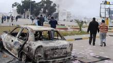 Residents are seen walking past a burned-out vehicle in Benghazi, Libya on Monday, Feb. 21, 2011. (Associated Press/AP)