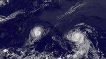 This image provided by NOAA taken Thursday Aug. 7, 2014 at 2 a.m. EDT shows Hurricane Iselle, left and Hurricane Julio. Iselle was supposed to weaken as it slowly trudged west across the Pacific. It didn't -- and now Hawaii is poised to take its first direct hurricane hit in 22 years. (ASSOCIATED PRESS)