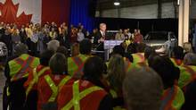 Prime Minister Stephen Harper speaks in front of Ford of Canada production workers at the Oakville Assembly Plant Jan. 4, 2013. The Canadian Auto Workers is trying to organize plants belonging to Toyota and Honda in Ontario. (STRINGER/REUTERS)