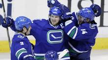 Vancouver Canucks' Henrik Sedin, centre, celebrates his goal against the Edmonton Oilers with teammates Kevin Bieksa, left, and Alex Burrows during the second period of their NHL hockey game in Vancouver on Saturday. (BEN NELMS)