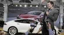 Tesla Motors CEO Elon Musk waves at the factory in Fremont, Calif. So far the electric car maker has been been a very profitable investment. (Paul Sakuma/AP)