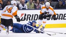 Philadelphia Flyers teammates Kimmo Timonen, left, and Sean Couturier, right, take out Toronto Maple Leafs forward Mikhail Grabovski, centre, during second period NHL hockey action in Toronto on Thursday, April 4, 2013. (The Canadian Press)