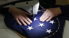 A worker sews stars on a U.S. national flag at the Waelkens flag company in Oostrozebek, Belgium Feb. 4, 2013. (FRANCOIS LENOIR/REUTERS)