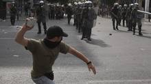 A protester throws a stone at policemen during riots in Athens this month. (JOHN KOLESIDIS/John Kolesidis/Reuters)