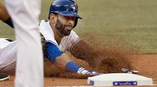 Jose Bautista gets tagged out at first base during a run down in the first inning. Bautista was moved from his usual spot in right field to designated hitter for Monday's game. (Nathan Denette/The Canadian Press)