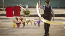 Police oversee the scene where four people were shot, two fatally, at a mill in Nanaimo, B.C. Red shirts and flowers left by mourners constitute a makeshift memorial. (John Lehmann/The Globe and Mail)